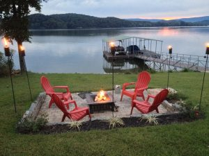 Campfire by the lake at dusk with pink adirondack chairs- Grande Vista Bay