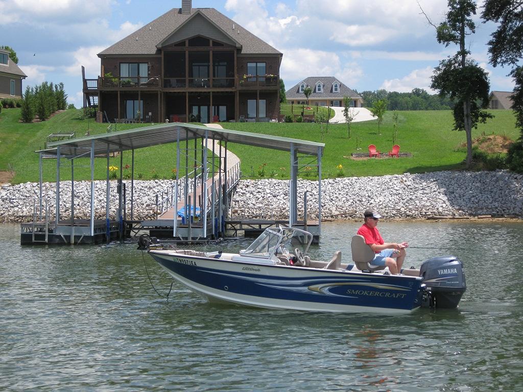 Fisherman in boat by dock at Grande Vista Bay