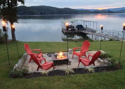 Pink adirondack chairs and fire pit at dusk.Grande Vista Bay Lakefront