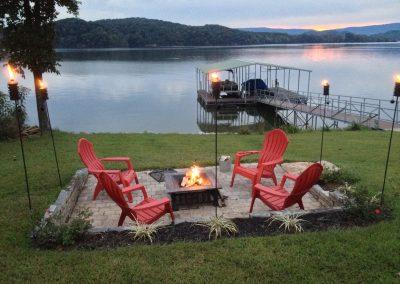 Pink adirondack chairs and fire pit at dusk.Grande Vista Bay Lakefront