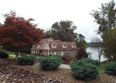 Home with multiple dormers lakefront with evergreens