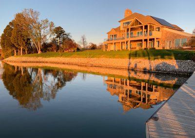 Golden light on Home on still lake at Grande Vista Bay