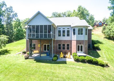 Rear elevation of two story home with yellow adirondack chairs and swing