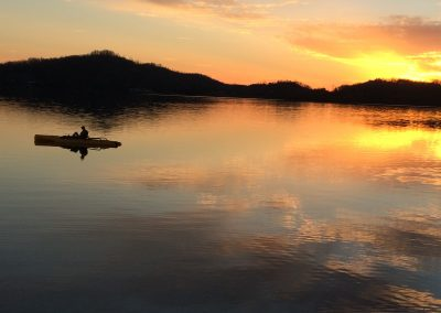 Lone man and canoe on lake at sunset.