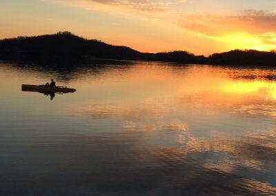 Lone man and canoe on lake at sunset.