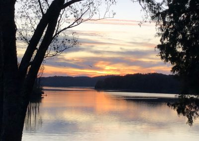 Sunrise or sunset on a calm Watts Bar Lake with trees in foreground.