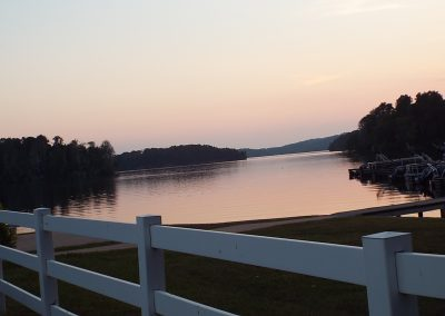 Dusk at the boat docks with white rail fence in foreground.