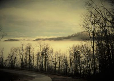 Heavy fog on lake in morning light. GBV sidewalk in foreground.