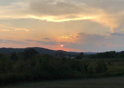 Mountain view at dusk, sun partially behind cloud.